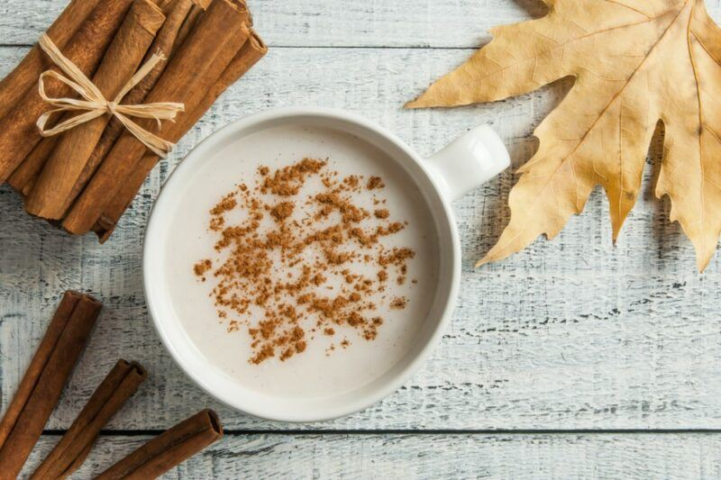 A white table with cinnamon sticks, a leafy, and porridge topped with cinnamon