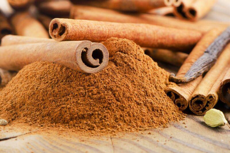 Some sticks of cinnamon on top of a pile of cinnamon