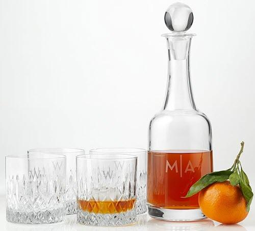 Four whiskey glasses and a decanter with an orange.