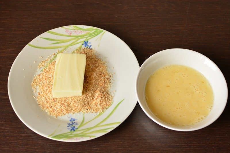 Coating the cheese with breadcrumbs and egg