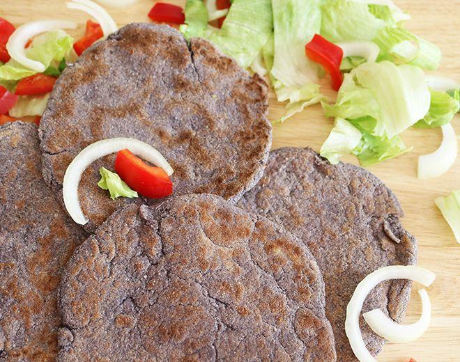 Dark flatbread with salad on a cutting board