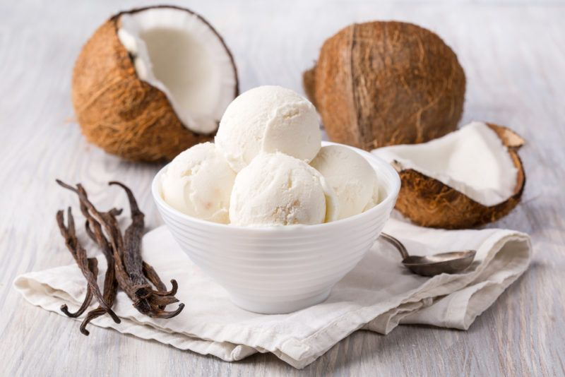 A white bowl of coconut ice cream in front of coconuts next to vanilla beans