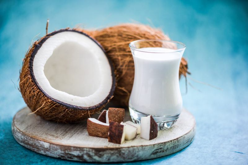 Coconut milk and coconuts on a wooden slab