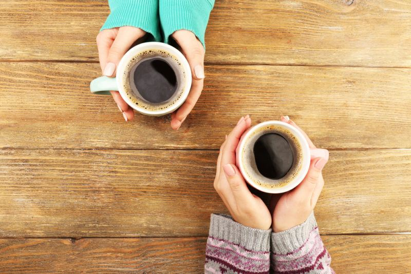 Two sets of hands and sleeves each holding a mug of black coffee