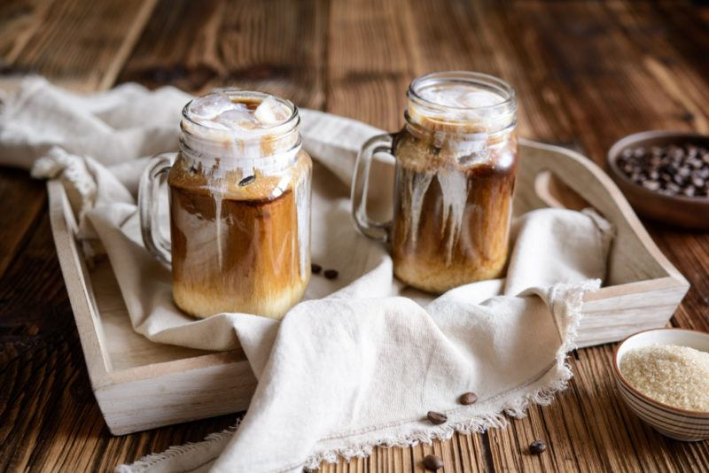 Two mugs of iced coffee made using heavy cream
