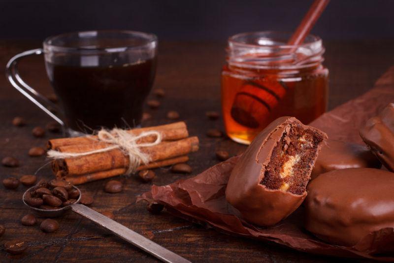A mug of coffee, with honey, cinnamon and chocolate biccies