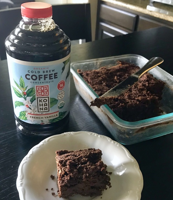 A glass container and a plate with brownies next to a cold brew bottle