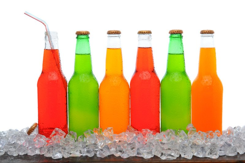 Soda of the Month Clubs - 6 colorful sodas in bottles the first one in line is missing the cap with a straw the bottles are sitting on ice.