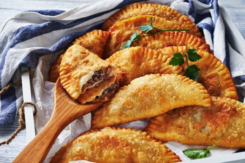 A collection of fried empanadas. One is on a spoon, has been cut open and is filled with meat