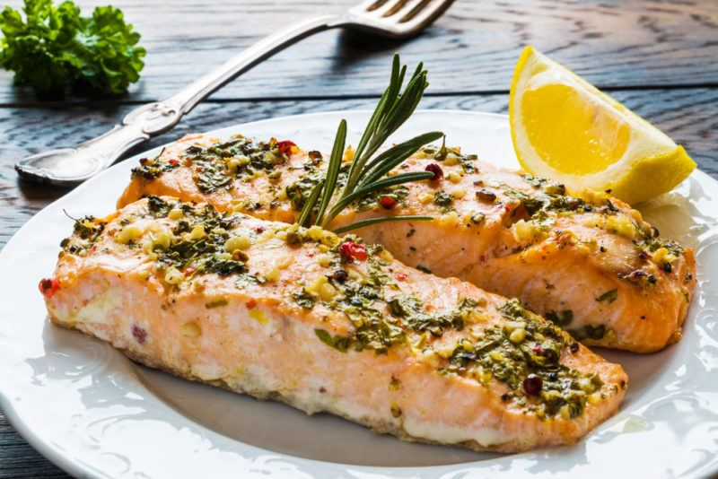 Two pieces of cooked salmon on a plate with rosemary and a fork
