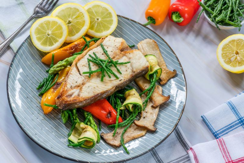 A light blue plate with cooked halibut, vegetables, and sliced lemons