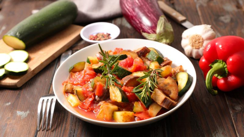 A bowl of cooked ratatouille with the various raw vegetables in the background