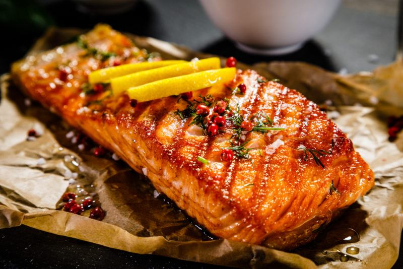 A piece of cooked salmon on paper with seasoning and lemon