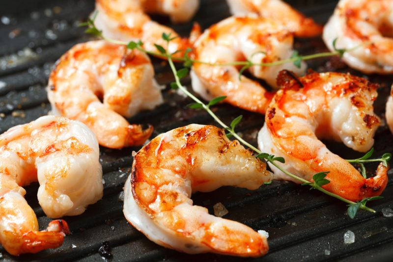 Half a dozen or so cooked shrimp on a grill