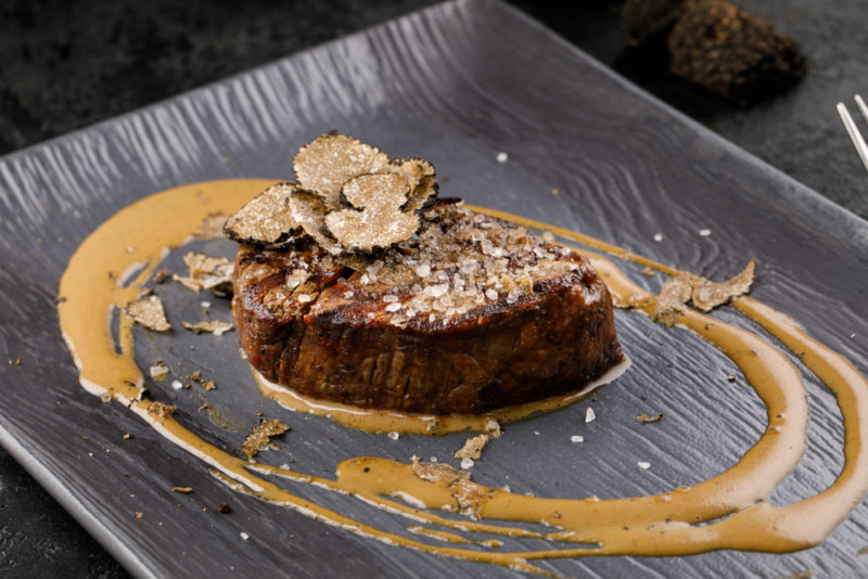 A black plate with a cooked steak and sliced truffles