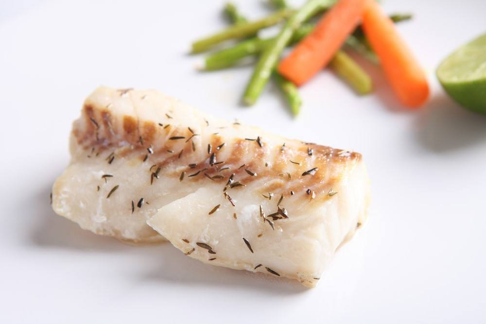 A small piece of cooked white cod on a white table in front of vegetables