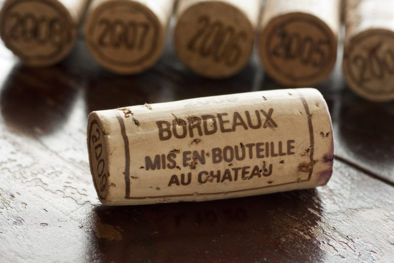 Corks from the Bordeaux region with one in the foreground and the tops of the other corks visible