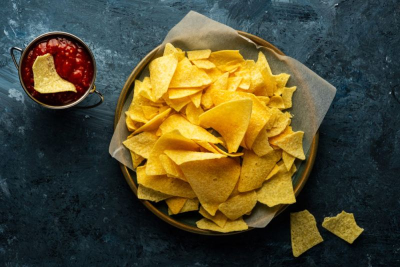 A dish containin fresh corn chips, next to a small bowl of salsa