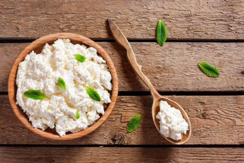 Top down image of a wooden bowl and wooden spoon containing cottage cheese