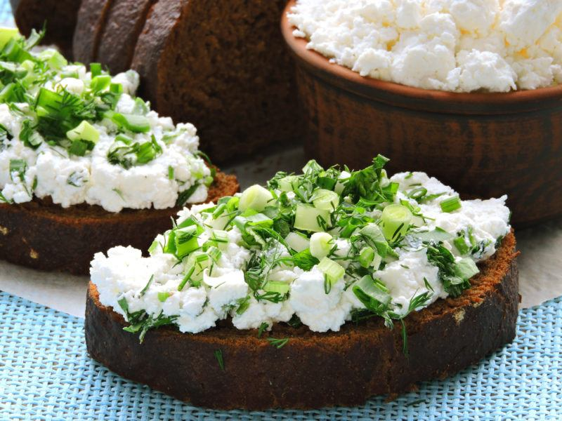 Toast with cottage cheese and greens, with a bowl of cottage cheese in the background