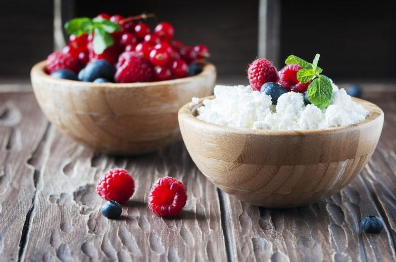 A wooden bowl of cottage cheese with another bowl of berries
