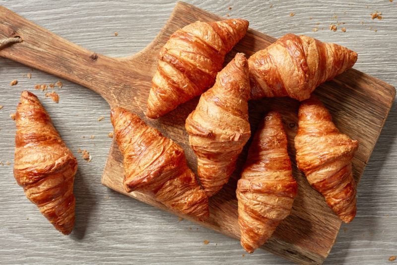 A wooden board containing various croissants