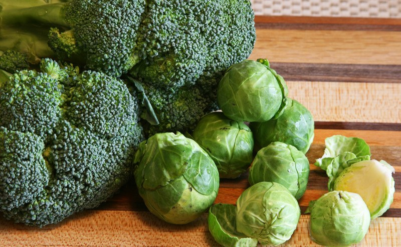 Two heads of broccoli and several brussels sprouts rest on a striped wooden countertop.