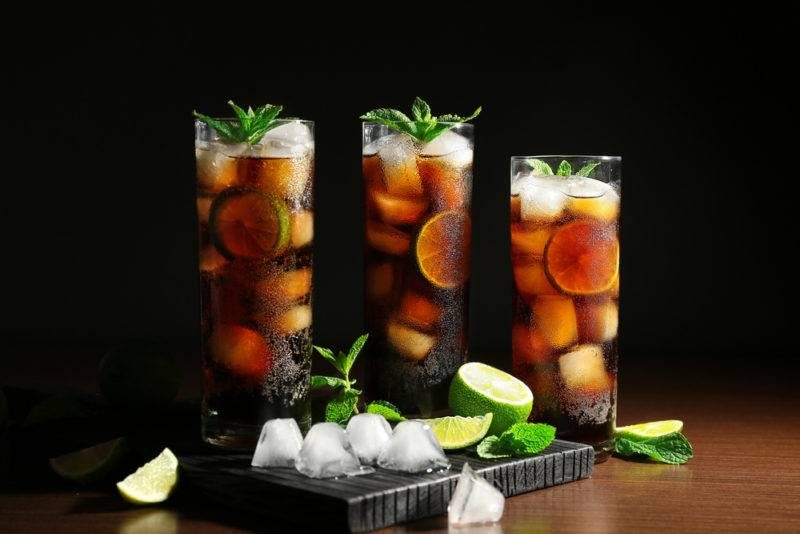 Three tall glasses of rum and coke with lime - a cuba libre