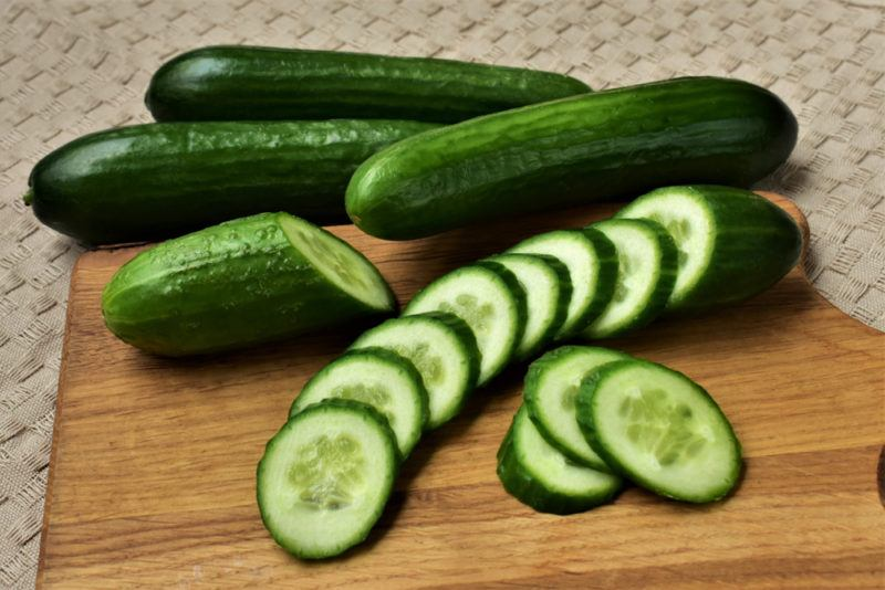 Long cucumbers and a sliced cucumber on a table