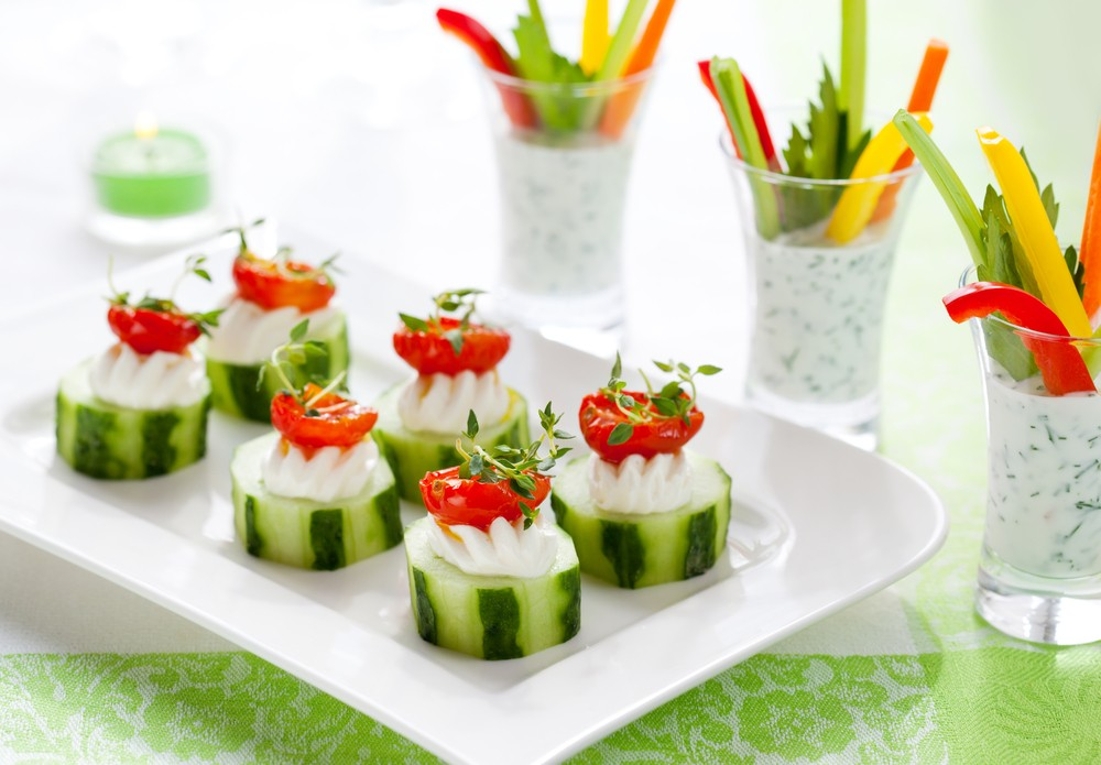 A white plate with eight pieces of sliced cucumber, with some type of cheese and cherry tomatoes, next to shot glasses filled with dip and sliced veggies