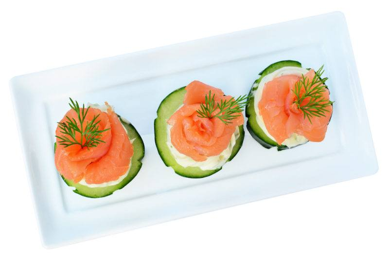 A white plate with appetizers of cucumber, salmon, and cream cheese