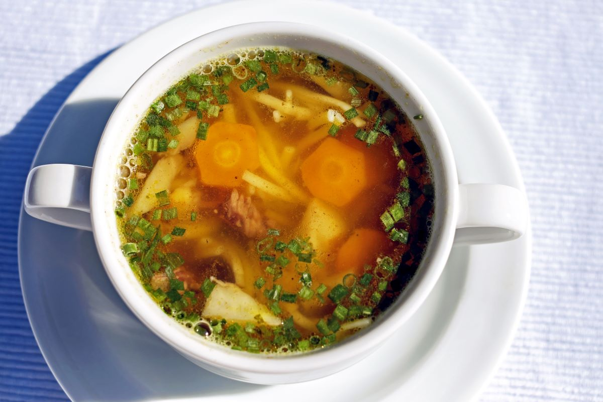 Vegetable beef soup with large carrot slices and other vegetables, in a double handled white ceramic mug