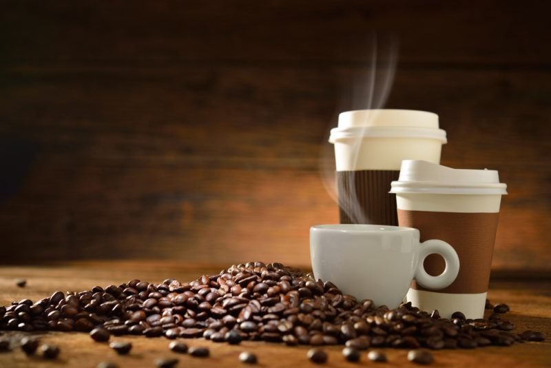 Three different types of coffee cups with steam rising, and coffee beans scattered across a table
