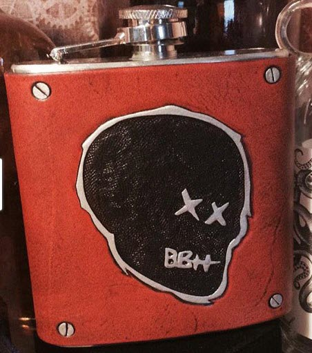 A stainless steel flask with a red cover and black skull.