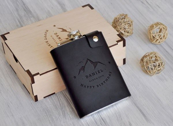 A dark leather flask with a mountain and text resting against a box with a similar engraving.