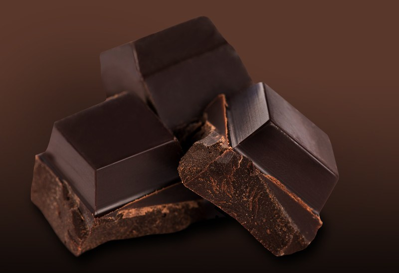 This photo shows three squares of dark chocolate against a brown background.