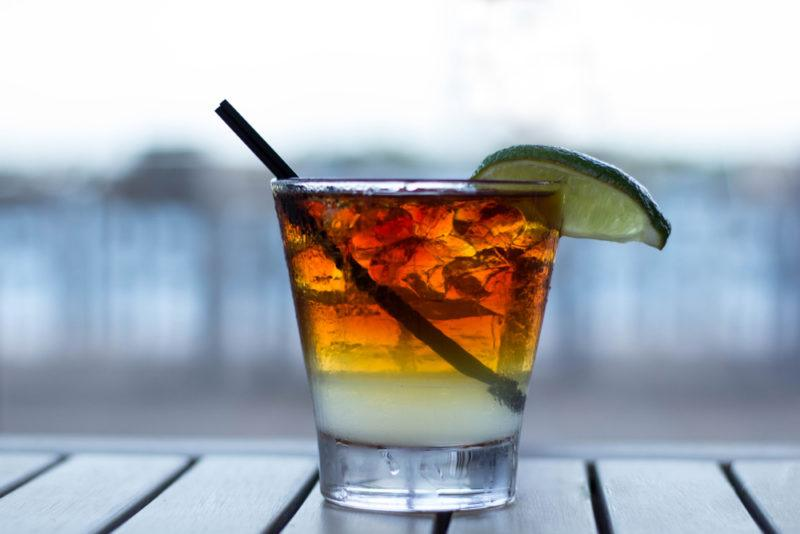 A dark and stormy coffee cocktail with a straw and a lime