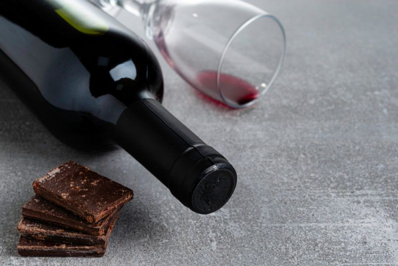 A small pile of dark chocolate, next to a bottle of red wine and a glass with a tiny bit of red wine
