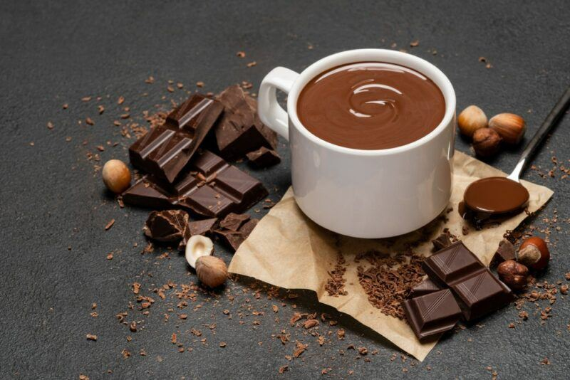 A dark table with a white mug of hot chocolate, with various pieces of dark chocolate