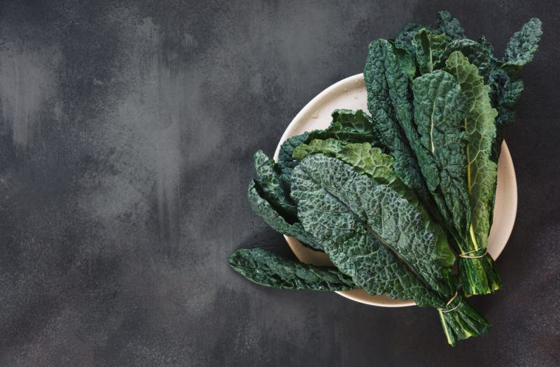 A plate on a chalk table with dark leafy greens