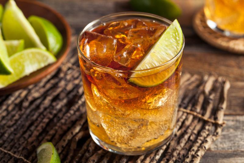 A dark and stormy cocktail with ice and lime