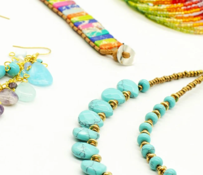 Turquoise Beaded necklace with matching beaded earrings, laid above bright colored bracelets