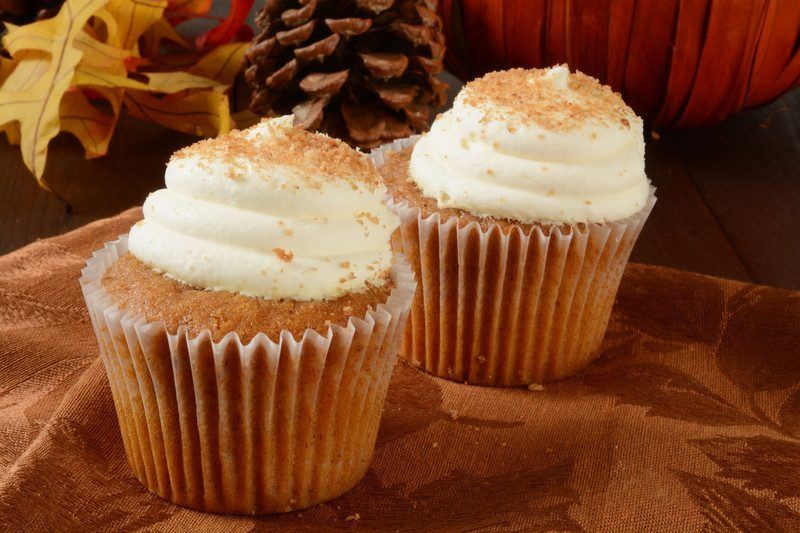 moist brown cupcakes with white frosting and raw sugar topping with fall themed background
