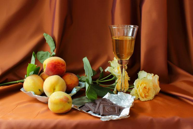 A glass of white dessert wine, some peaches, peach-colored roses, and milk chocolate