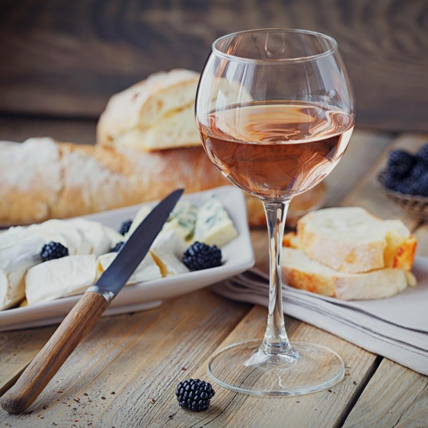 Sweet rose wine with bread, cheese and black berries in the background, with a knife resting on the plate of cheese