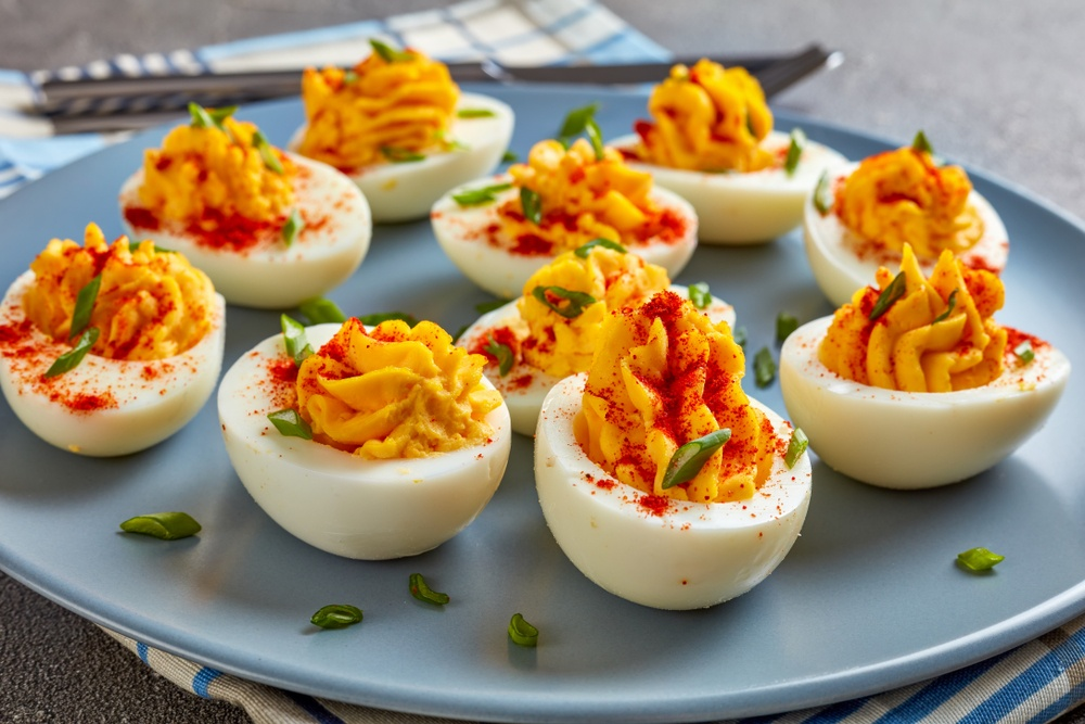 A blue plate with deviled eggs and paprika