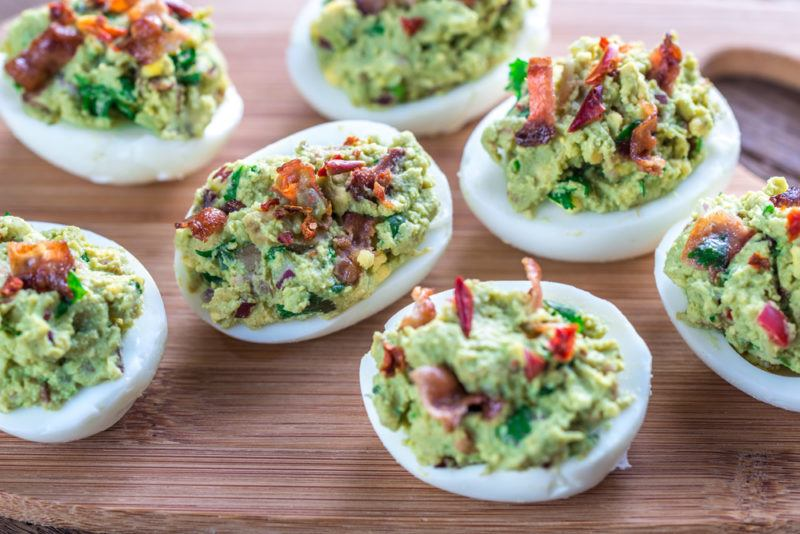 Deviled eggs on a table that have been made using guacamole and bacon