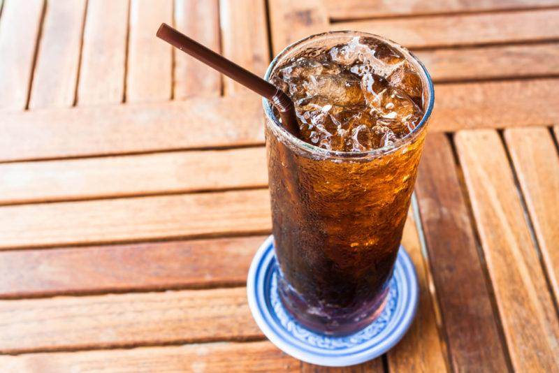 A glass of diet cola on a coaster on a wooden table with a straw