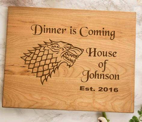 A cutting board with 'Dinner is Coming' and Game of Thrones information on it.