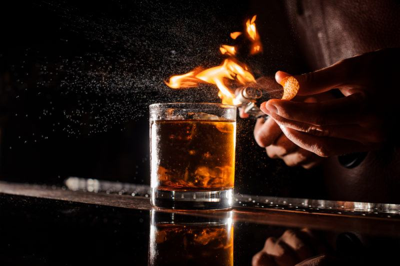 A Don Lockwood whiskey cocktail on a bar with a bartender making a flaming orange peel